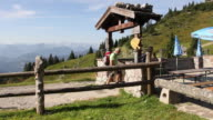 MS PAN Hikers are entering an Alm on mountain top with Bavarian Alps in background / Lenggries, Bavaria, Germany