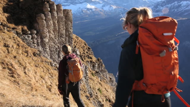 Hikers climb slope above valley and mountains