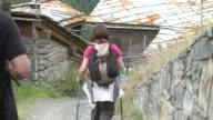 MS Hikers getting down mountain through village at findeln / Zermatt, Valais, Switzerland