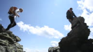 'Hikers jump between rocks on ridge crest, reach summit'