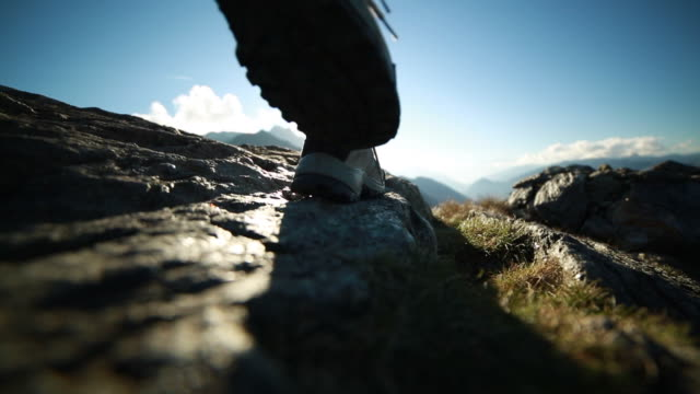 Hikers reaching top of mountain, boots close up