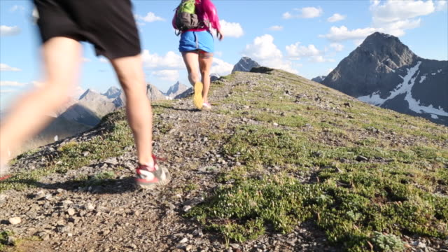 Hikers run along high ridge crest, above mountains