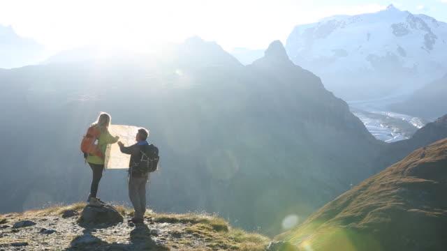 Hiking couple check map, watching sunrise over mtns.