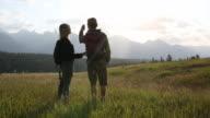 Hiking couple cross mountain meadow, take smart phone pic