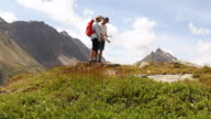Hiking couple examine trail map, in mountains
