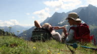 Hiking couple relax in alpine meadow, apply sunscreen