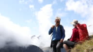Hiking couple relax on mountain slope, look out