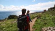 Hiking couple walk along pathway near sea edge