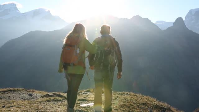 Hiking couple walk towards sunrise over mtns.