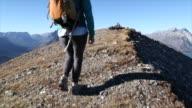 POV of hiking couple walking along ridge, reaching summit