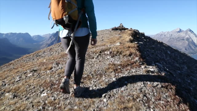 POV of hiking couple walking along ridge, reaching summit
