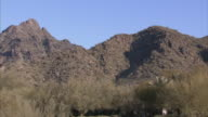 Hills w/ dry grass cacti some trees lower frame FG possibly part of Phoenix Mountains AZ