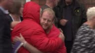 Six people charged with criminal offences ENGLAND Cheshire Warrington EXT Men hugging Women hugging Man waving and fist pumping as along with others...