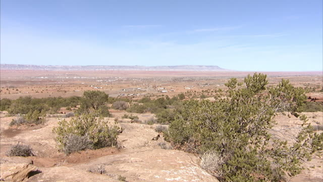 Scattered structures town in valley blue sky rocky landscape terrain w/ green shrubs plants FG plateau mesa mountain BG Southwest arid dry desert...