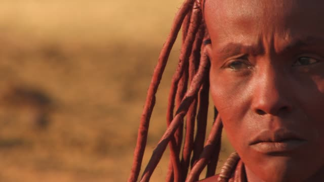 A Himba woman puts otjize on herself. Available in HD.