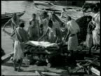 FUNERAL Hindu men placing wrapped body on logs by Ganges River funeral pyre Smoking pyre w/ sticks covering body