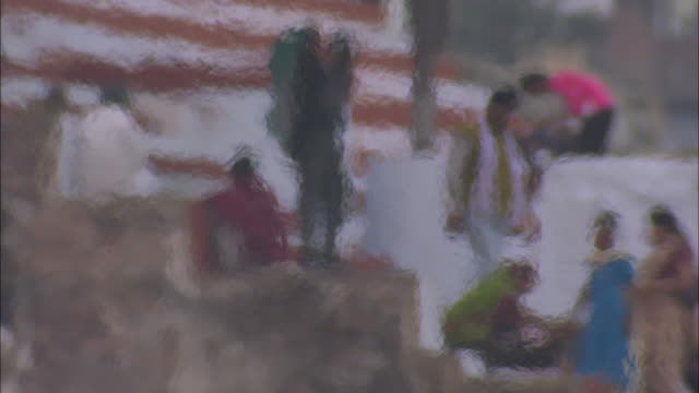 Hindus climb down ghats as heat waves from a fire blur the scene.