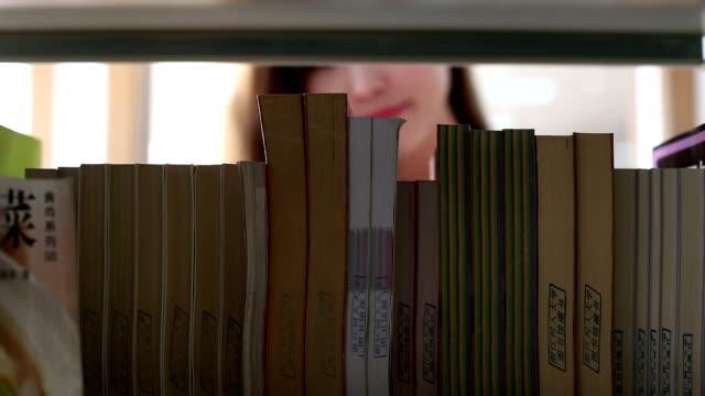 hinese Studentin look für Buchen Sie im Bücherregal in Bibliothek, Echtzeit.