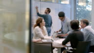 Hip young businessman leads meeting in office conference-room, points out numbers on white-board (dolly shot)