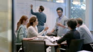 Hip young businessman leads meeting in office conference-room (dolly shot)
