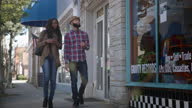 WS. Hip young couple walk up downtown street and point out local record store on sunny day.