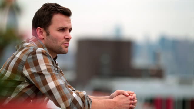 Hip young man stands alone on Brooklyn rooftop (dolly-shot)