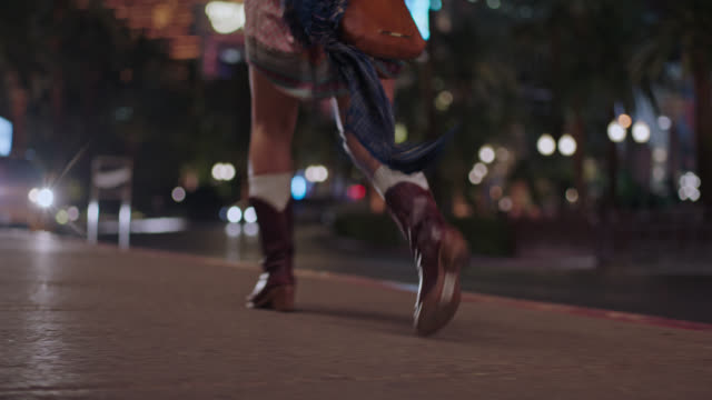 Hip young woman in vintage dress and cowboy boots walks and skips down Las Vegas strip at night.