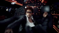 Hip-hop star dances wildly for camera in back of limousine at awards show