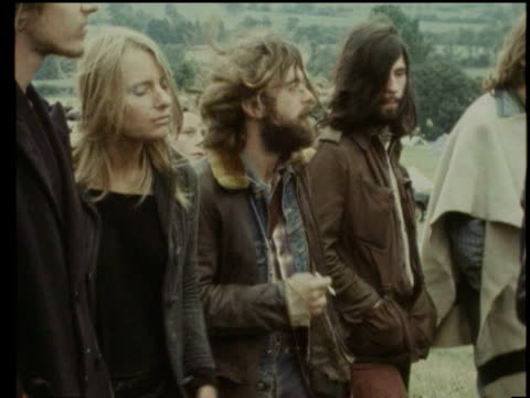 Hippies playing music at Glastonbury Festival / WS Hippies arriving in town / MS Locals driving past in cars / Glastonbury England