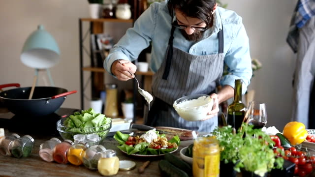 Hipster toevoegt dressing aan de salade