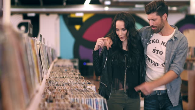 A hipster couple walks though a record store shopping.