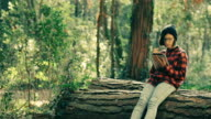 Hipster girl using digital tablet in the forest