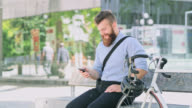 DS Hipster having a video call while sitting on a bench in the city
