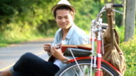 Hipster man traveling with vintage bicycle and playing ukulele