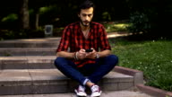 Hipster sitting on steps in park