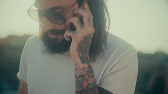 Hipster tattooed rebel guy using mobile phone