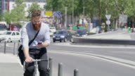 WS Hipster text messaging while riding a bike in the city