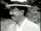 Hirohito walking in garden w/ Empress Dowager Nagako CU Hirohito laughing CU Nagako w/ parasol WS Young Masohito Akihito by lake swimming VS Hirohito...
