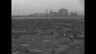 Hiroshima street with rubble on either side after atomic bomb blast during World War II / man stands amid rubble / rubble lying about with puddle of...