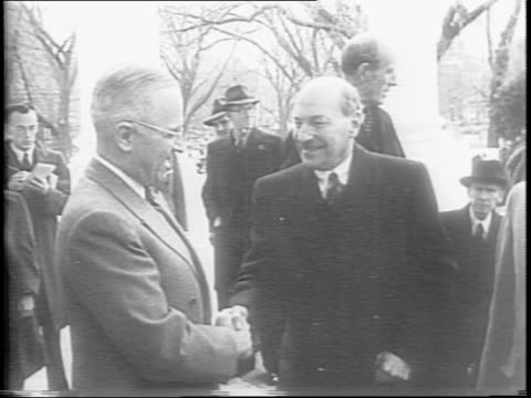 His car stopped at the White House Prime Minister Clement Attlee springs from his vehicle and approaches President Harry Truman shaking hands when...