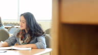 Hispanic adult male and female students studying together at table in college library
