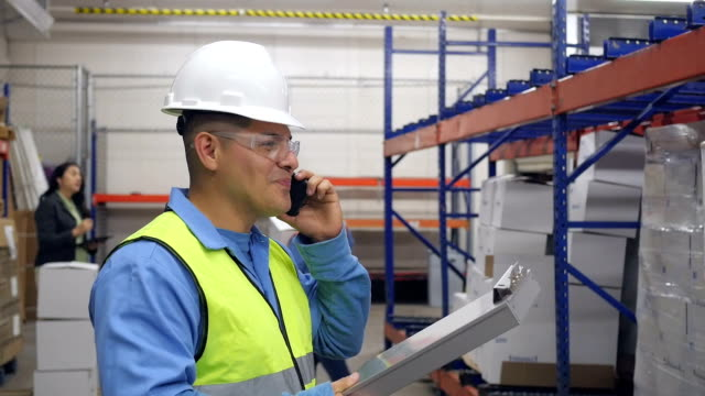 Hispanic blue collar worker in warehouse taking shipment order over phone
