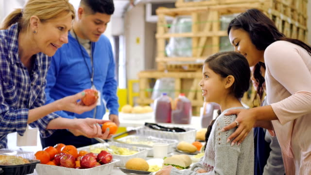 Hispanic child choosing healthy food in line at soup kitchen