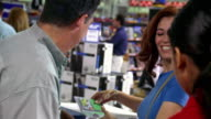 MS PAN Hispanic couple buying computer + software at checkout with female cashier