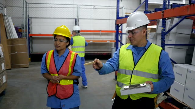 Hispanic coworkers doing inventory in shipping distribution warehouse