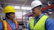Hispanic coworkers talking in shipping distribution warehouse
