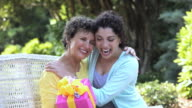 PAN hispanic daughter greeting mother with present, Richmond, Virginia, United States