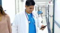 Hispanic doctor checking smart phone in hospital hallway