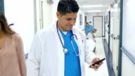 Spaanse arts controleren slimme telefoon in de hal van het ziekenhuis