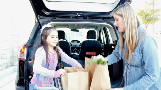 Hispanic elementary age daughter is helping mother load brown paper grocery bags in minivan or SUV outside of grocery store